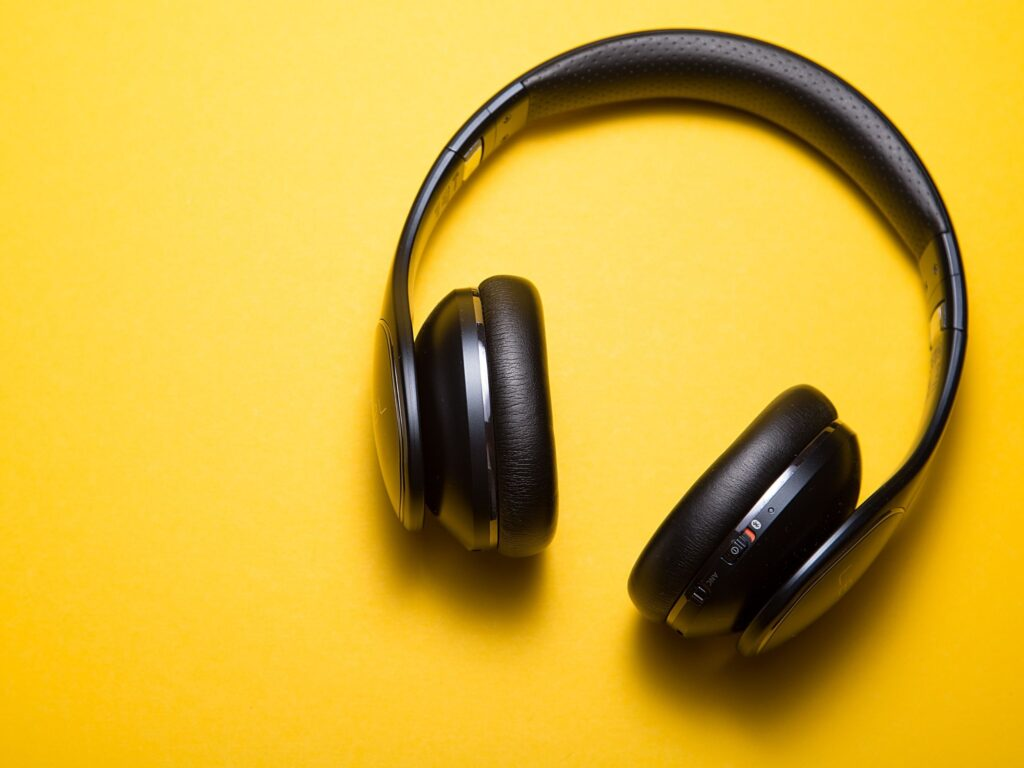 Foto de um fone de ouvido para escutar podcast em um fundo amarelo.