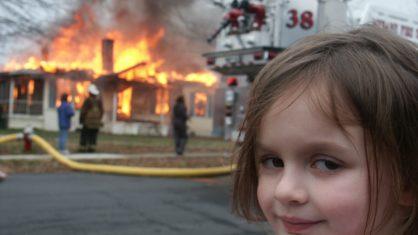 Garota sorri em frente a uma casa em chamas.
